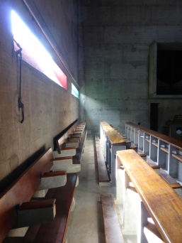 Pews, getting light from slit windows, whose sides are painted different colours