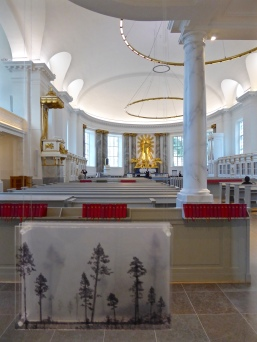 Göteborg cathedral: singer rehearsing in the choir, with painted forest scenes in the foreground